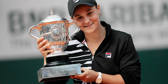 Australia's Ashleigh Barty holds the trophy as she celebrates winning her women's final match of the French Open tennis tournament against Marketa Vondrousova of the Czech Republic in two sets 6-1, 6-3, at the Roland Garros stadium in Paris, Saturday, June 8, 2019.
