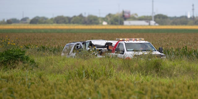 Law enforcement move a vehicle as they investigate a fatal wreck that left six migrants dead and several others injured outside Robstown, Texas on Wednesday, June 5, 2019. (Courtney Sacco/Corpus Christi Caller-Times via AP)