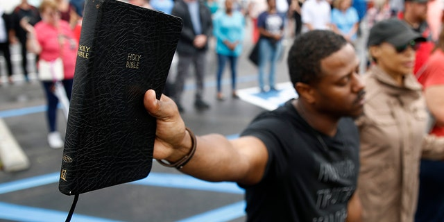 Mike Harris, of Virginia Beach, Va., holds a Bible as he prays during a vigil in response to a shooting at a municipal building. A longtime city employee opened fire at the building Friday before police shot and killed him, authorities said. (AP Photo/Patrick Semansky)