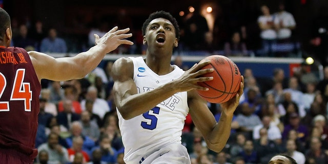 In this March 29, 2019, file photo,Duke forward RJ Barrett (5), from Canada, drives to the basket past Virginia Tech forward Kerry Blackshear Jr. (24) and guard Ahmed Hill (13) during the second half of an NCAA men's East Regional semifinal college basketball game, in Washington. (AP Photo/Alex Brandon, File)