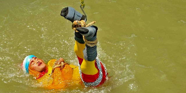 "In this photo taken on June 16, 2019 Indian stuntman Chanchal Lahiri, known by his stage name ""Jadugar Mandrake"", is lowered into the Ganges river, while tied up with steel chains and ropes, in Kolkata. - An Indian magician who went missing after being lowered into a river tied up in chains and ropes in a Houdini-inspired stunt is feared drowned, police said June 17. (Photo by STR / AFP) (Photo credit should read STR/AFP/Getty Images)"