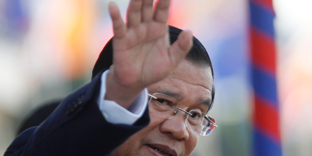 FILE - In this Nov. 21, 2018, file photo, Cambodia's Prime Minister Hun Sen waves as he watches boat races during the water festival in Phnom Penh, Cambodia. The bitter decadeslong rivalry between Hun Sen, Cambodia's strongman leader, and Sam Rainsy, the self-exiled chief political rival and critic, has sometimes played out in deadly violence. But on Sunday, soup rather than blood was likely to be spilled. (AP Photo/Heng Sinith, File)