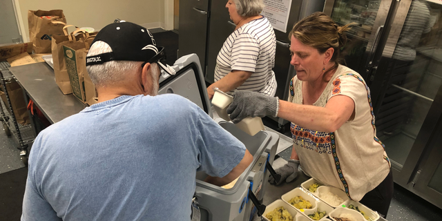 In this photo taken Friday, June 14, 2019, volunteers including Shelley Winship and retired accountant Ralph Nava, left, pick up food packages to deliver to homebound families and dependent children in Santa Fe, N.M., at the headquarters for Kitchen Angels. An annual report on childhood well-being from the Annie E. Casey Foundation ranks New Mexico last among 50 states that includes measures of poverty, health care, education and family support. The number of children living in poverty has swelled over the past three decades in fast-growing, ethnically diverse states such as Texas, Arizona and Nevada as the nation's population center shifts south and west. (AP Photo/Morgan Lee)