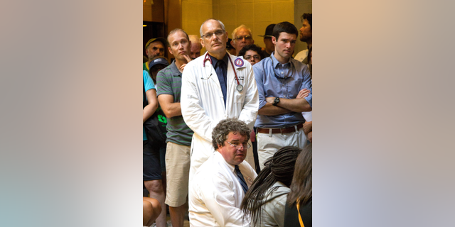 In this July 23, 2013, photo provided by Jenny Warburg, Dr. Charles van der Horst, standing at center, joins a Moral Monday protest at the state legislative building in Raleigh, N.C. Police were searching Saturday for the retired medical school professor and AIDS researcher from North Carolina who went missing during a marathon swimming race down New York's Hudson River. Tim Tyson sits before Van der Horst. (Jenny Warburg via AP)