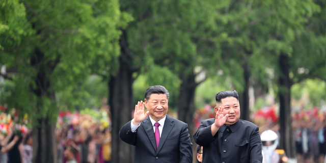 In this Thursday, June 20, 2019, photo released by China's Xinhua News Agency, visiting Chinese President Xi Jinping, left, and North Korean leader Kim Jong Un wave from an open top limousine as they travel along a street in Pyongyang, North Korea. (Associated Press)