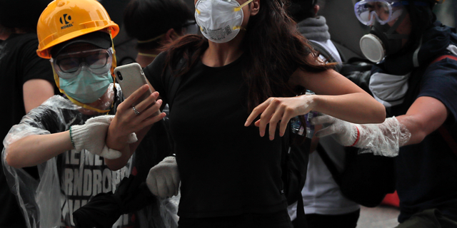 Protesters flee after police fired tear gas during a massive demonstration outside the Legislative Council in Hong Kong onJune 12, 2019. (AP Photo/Kin Cheung)