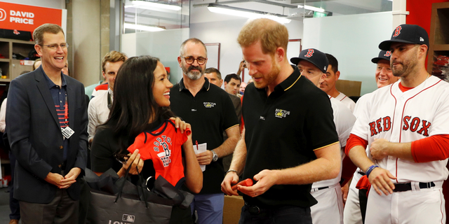 Duchess Meghan (L) and Prince Harry (R) are gifted a onesie from the Boston Red Sox.