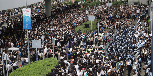 Protesters accumulate in front of policemen in anti-riot rigging outward a Legislative Council in Hong Kong, Wednesday, Jun 12, 2019. Government officials in Hong Kong are fresh for a showdown as protesters and military continue to face off into a early morning hours outward a semiautonomous Chinese territory's legislature forward of Wednesday's discuss over changes permitting extradition to a Chinese mainland. (AP Photo/Vincent Yu)