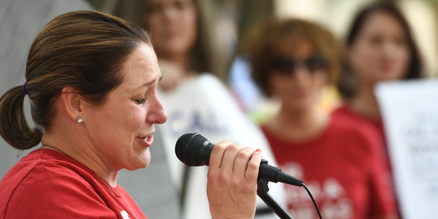 Jules Woodson, of Colorado Springs, Colo., speaks during a rally outside the Southern Baptist Convention's annual meeting Tuesday, June 11, 2019, in Birmingham, Ala. First-time attendee Woodson spoke through tears as she described being abused sexually by a Southern Baptist minister. (AP Photo/Julie Bennett)