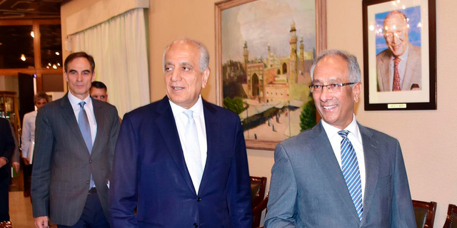 In this photo released by the Foreign Office, Pakistan's Foreign Ministry official Aftab Khokhar, right, escorts visiting Special Representative for Afghanistan Reconciliation Zalmay Khalilzad, center for talks at the Foreign Office in Islamabad, Pakistan, Sunday, June 2, 2019. Khalilzad has met Pakistani officials to find a peaceful solution to the neighboring Afghanistan war