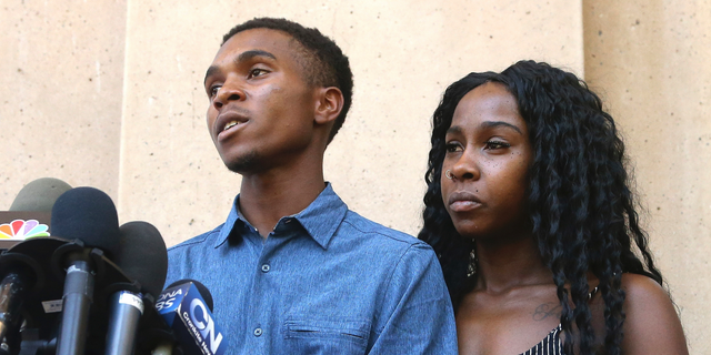 Dravon Ames, left, answers a question as Iesha Harper, right, joins her fiancee during a news conference at Phoenix City Hall, Monday, June 17, 2019, in Phoenix. Ames and his pregnant fiancée, Harper, who had guns aimed at them by Phoenix police during a response to a shoplifting report, say they don't accept the apologies of the city's police chief and mayor and want the officers involved to be fired. (AP Photo/Ross D. Franklin)