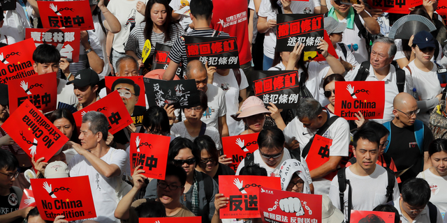 Protesters hold placards march in a rally against the proposed amendments to extradition law in Hong Kong, Sunday, June 9, 2019.  (AP Photo/Kin Cheung)