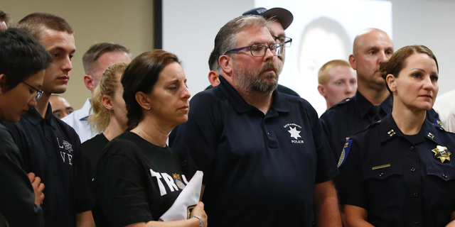 With their eyes closed, Kelly and Denis O'Sullivan, the parents of slain Sacramento Police officer Tara O'Sullivan, hold hands during a news conference in Sacramento, Calif., Tuesday, June 25, 2019. (AP Photo/Rich Pedroncelli)