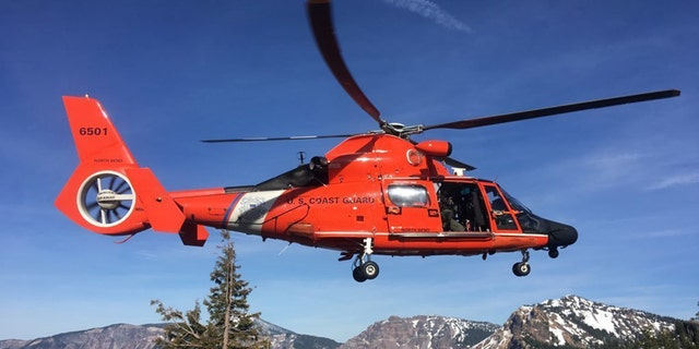 An MH-65 Dolphin helicopter landing at a Crater Lake parking area to transfer the injured man to AirLink Critical Care Transport on Monday. (U.S. Coast Guard photo courtesy of Sector North Bend)