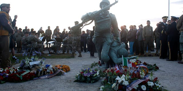 Floral tributes are placed at the National Guard Monument Memorial as members of the United States Army Europe Band and Chorus play in the background near Omaha Beach, in Normandy, France, on Thursday. (AP)