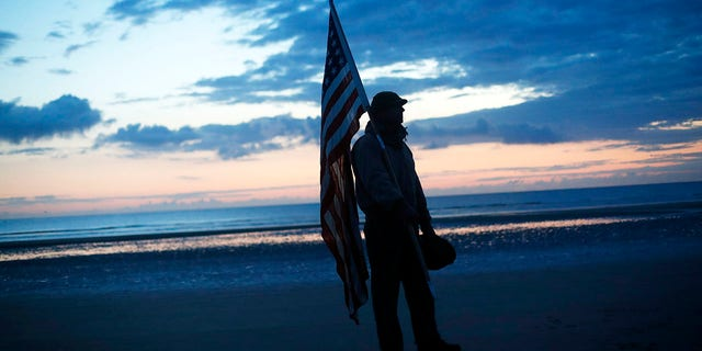 Udo Hartung from Frankfurt, Germany, a World War II reenactor, holds the U.S. flag as he stands at dawn on Omaha Beach, in Normandy, France on Thursday. (AP)