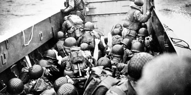 Troops crouch inside a LCVP landing craft, just before landing on Omaha Beach on D-Day, 6 June 1944. Photograph from the U.S. Coast Guard Collection in the U.S. National Archives.
