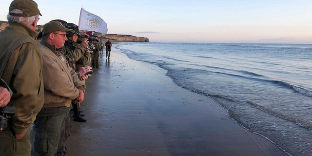 Re-enactors stand at the shore of Omaha Beach at sunrise as part of events to mark the 75th anniversary of D-Day on Omaha Beach in Vierville-sur-Mer, Normandy, France, Thursday, June 6, 2019. (Cedric Lecoz via AP)