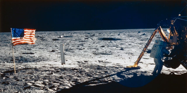 Neil Armstrong is shown beside the Lunar Module. Also visible are the U.S. flag and the solar wind experiment which was flown on all the Apollo missions.