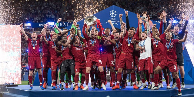 FC Liverpool players celebrate with the trophy after winning the UEFA Champions League Final between Tottenham Hotspur and Liverpool at Estadio Wanda Metropolitano on Saturday in Madrid. (Getty Images)