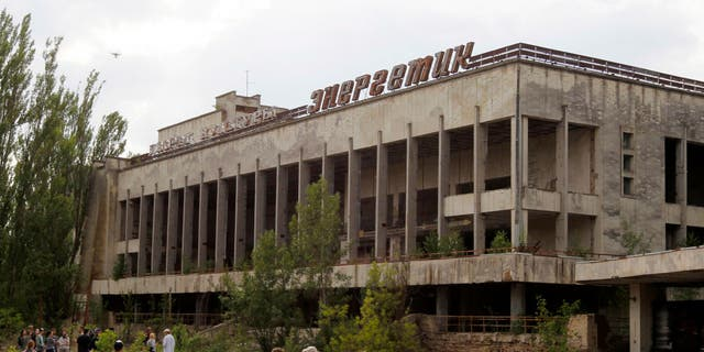 """Visitors look in the abandoned city of Pripyat, near the Chernobyl nuclear power plant, in June 2019. Tourist companies in the area have reported a sharp increase in the number of bookings since HBO's """"Chernobyl"""" debuted."""