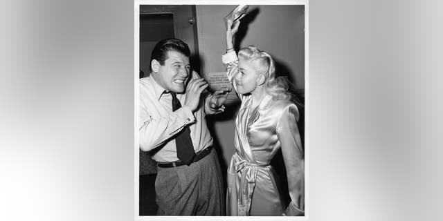 "Jack Carson winces as Doris Day is about to hit him with her shoe off camera from the film ""My Dream is Yours,"" circa 1949.<br>