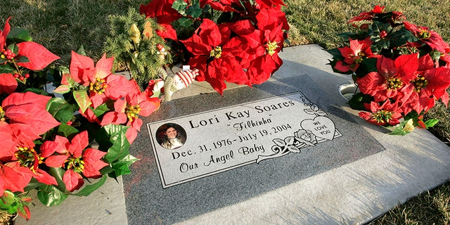 Flowers and a Christmas decoration surround the grave of Lori Hacking in the Orem City Cemetery, minus the Hacking family name Dec. 6, 2004, in Orem, Utah. (Photo by George Frey/Getty Images)