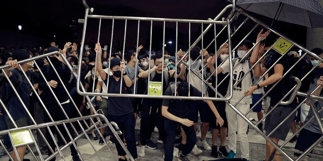 Protesters use barriers against the proposed amendments to the extradition law at the Legislative Council in Hong Kong during the early hours of Monday, June 10, 2019.