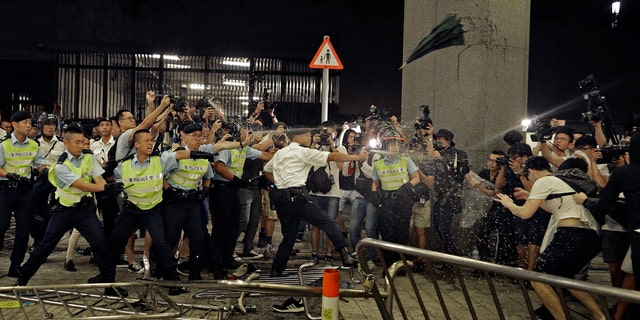 Police officers use pepper spray against protesters in a rally against the proposed amendments to the extradition law at the Legislative Council in Hong Kong during the early hours of Monday, June 10, 2019.