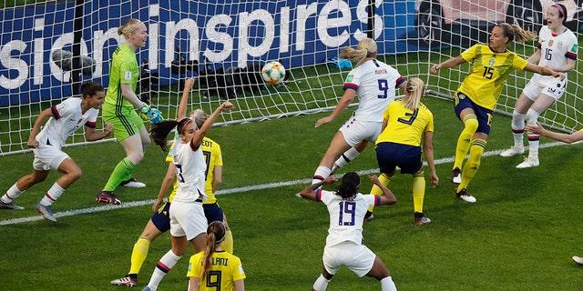 Lindsey Horan (9) wheels away after scoring the opening goal as her teammates celebrate. (AP Photo/Christophe Ena)