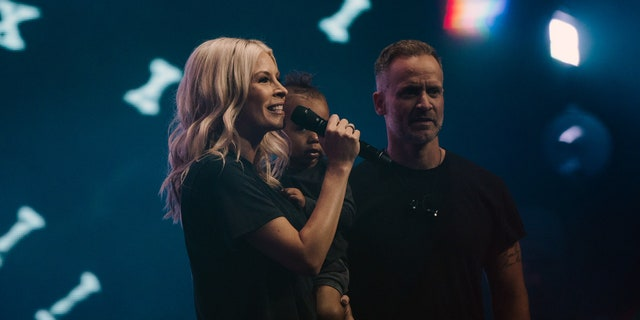 """Jenn Johnson speaks on the opening night of """"Heaven Come"""" in downtown Los Angeles May 23, 2019, holding her adopted son, Ryder Moses, and alongside her husband, Brian."""