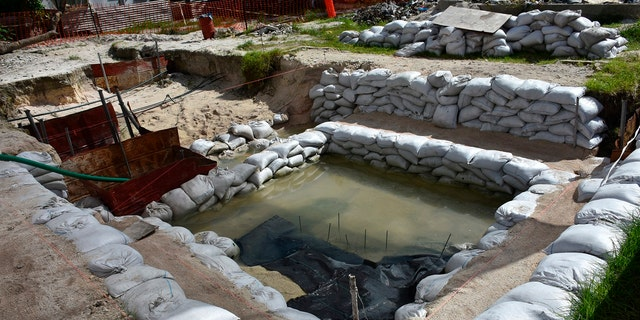 This June 1, 2019 photo provided by History Flight shows graves of U.S. servicemen under the water table in Tarawa, Kiribati. (Eric Albertson/Defense POW/MIA Accounting Agency/History Flight via AP)