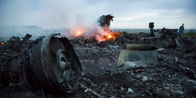 In this Thursday, July 17, 2014 file photo, a man walks amongst the debris at the crash site of a passenger plane near the village of Hrabove, Ukraine.