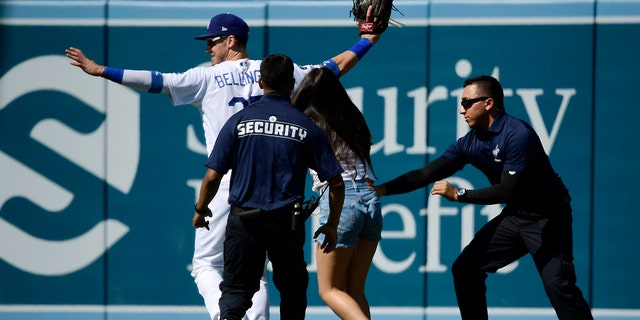 A fan is grabbed by security as she approaches Los Angeles Dodgers right fielder Cody Bellinger during the ninth inning of a baseball game against the Colorado Rockies, Sunday, June 23, 2019, in Los Angeles. (AP Photo/Mark J. Terrill)