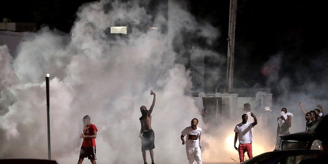 Frayser community residents taunt authorities as protesters take to the streets in anger against the shooting of a youth identified by family members as Brandon Webber by U.S. Marshals earlier in the evening, Wednesday, June 12, 2019, in Memphis, Tenn. (Associated Press)