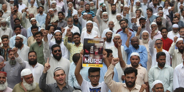 Supporters of the Pakistani religious party Jamaat-i-Islami, gather to offer a funeral prayer in absentia for ousted former Egyptian President Mohammed Morsi, in Karachi, Pakistan. Tuesday, June 18, 2019.