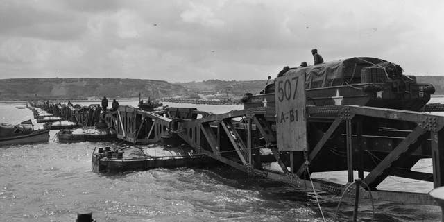 File photo - 'Mulberry', the secret floating harbor being put to good use on Omaha beach in Normandy as a large truck drives over one of the pontoons. Mulberry was later destroyed by channel storms.