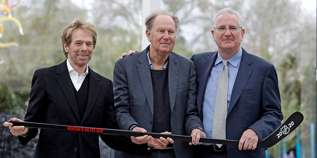 FILE - In this April 11, 2018, file photo, part-owners, from left to right, Jerry Bruckheimer and David Bonderman pose with Tod Leiweke and a hockey stick during a news conference naming Leiweke as the president and CEO for a prospective NHL expansion team in Seattle. (AP Photo/Elaine Thompson, File)