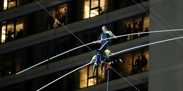 Aerialists Nik Wallenda, top, stepping over his sister Lijana as they walked on the high wire above Times Square on Sunday. (AP Photo/Jason Szenes)