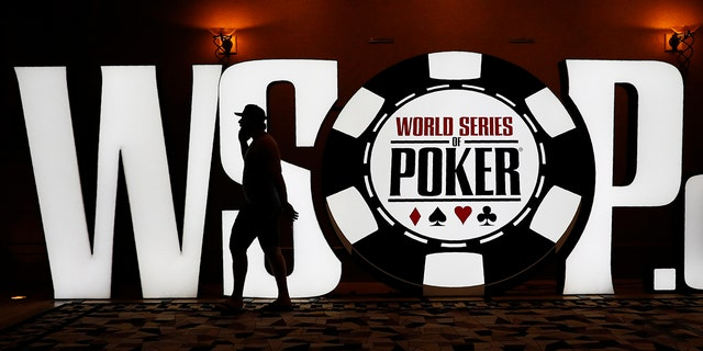 FILE - In this Monday, June 24, 2019, file photo, shows a man walking by a sign at the World Series of Poker in Las Vegas. Tens of thousands of professional and amateur poker players go on a pilgrimage to Las Vegas every summer in hopes of returning home richer, owning a gold bracelet and earning considerable bragging rights. They all want to win at the World Series of Poker. The tournament is marking its 50th year. The $10,000 buy-in, no-limit Texas Hold 'em main event kicks off Wednesday, July 3. (AP Photo/John Locher, File)