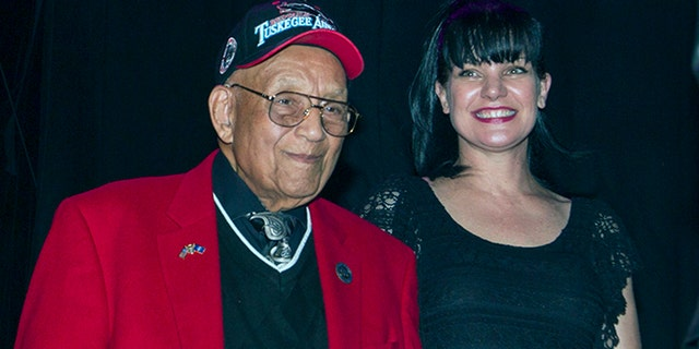 Lt. Col. Bob Friend, a Tuskegee Airman, stands onstage with actress Pauley Perrette during a benefit concert at The House of Blues in Los Angeles in 2013. (Photo by Paul A. Hebert/Invision/AP, File)
