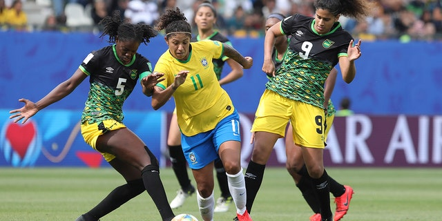 Brazil's Cristiane, center, competes for the ball with Jamaica's Konya Plummer, left, and Jamaica's Marlo Sweatman during the Women's World Cup Group C soccer match between Brazil and Jamaica in Grenoble, France, Sunday, June 9, 2019. (AP Photo/Laurent Cipriani)