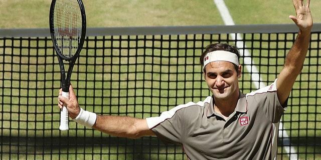 Swiss Roger Federer celebrates after winning the tennis ATP final against Belgium David Goffin in Halle, Germany, Sunday, June 23, 2019. (Friso Gentsch/dpa via AP)