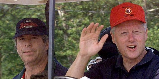 President Clinton waves to reporters as he and brother-in-law Tony Rodham, left, drive off for a round of golf at Maple Run Golf Course Saturday, Aug. 14, 1999, in Thurmont, Md. (AP Photo/Khue Bui)