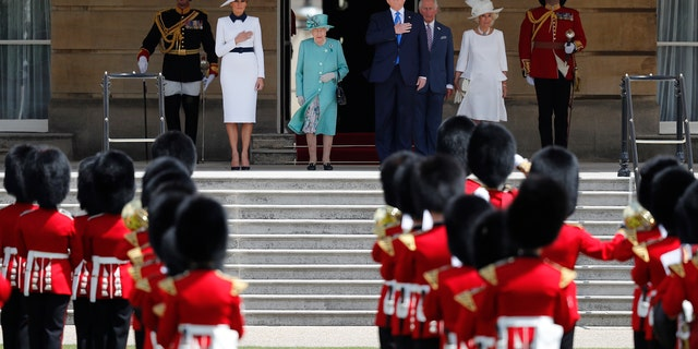 Britain's Queen Elizabeth II, President Trump, first lady Melania Trump, Britain's Prince Charles and Camilla, Duchess of Cornwall, listening to the U.S. national anthem during a ceremonial welcome in the garden of Buckingham Palace. (AP Photo/Frank Augstein)