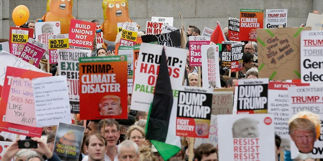People carry signs and banners as they gather in Trafalgar Square, central London, to demonstrate against the state visit of President Donald Trump, Tuesday. (AP Photo/Tim Ireland)
