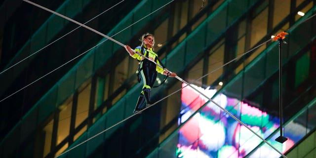 Aerialist Lijana Wallenda walks on a high wire above Times Square, Sunday, June 23, 2019, in New York. (AP Photo/Jason Szenes)