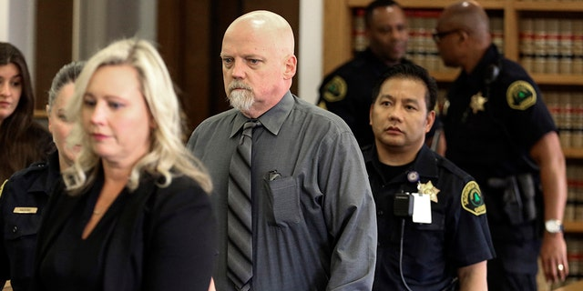 William Talbott II, center, is escorted to his seat Friday, June 28, 2019, at the Snohomish County Courthouse in Everett, Wash. William Earl Talbott II has been found guilty in the 1987 killings of a young Canadian couple, Tanya Van Cuylenborg and Jay Cook. (Kevin Clark/The Herald via AP, Pool)