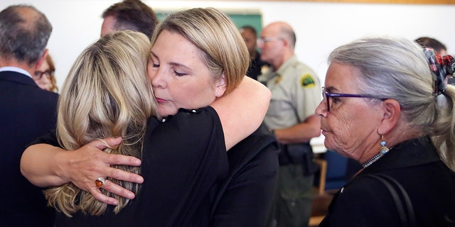 May Robson gets a hug from Kelly Cook, left, with Lee Cook, right, after William Talbott II was found guilty, Friday,  in the 1987 killings of Jay Cook and Tanya Van Cuylenborg, a young Canadian couple. (Kevin Clark/The Herald via AP, Pool)