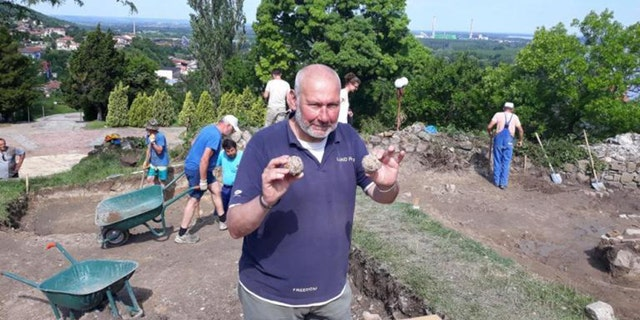 Lead archaeologist Nikolay Ovcharov showcases Vlad Dracula's alleged culverin cannonballs and other artifacts discovered during the renewed excavations of the Zishtova Fortress in Bulgaria's Svishtov. (Credit: Svishtov Municipality)